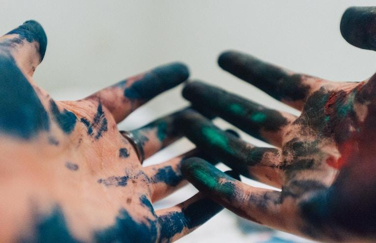 Creativity and spirituality pictured as a woman's hands covered in paint.