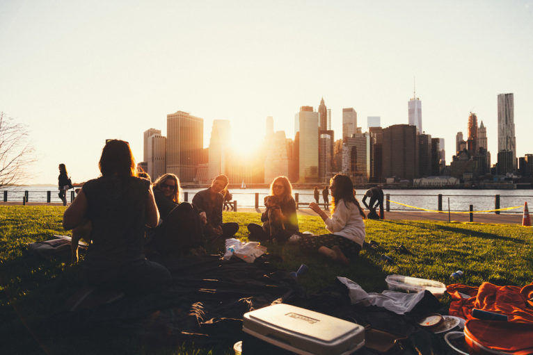 A group of friends sitting on the grass in a city park