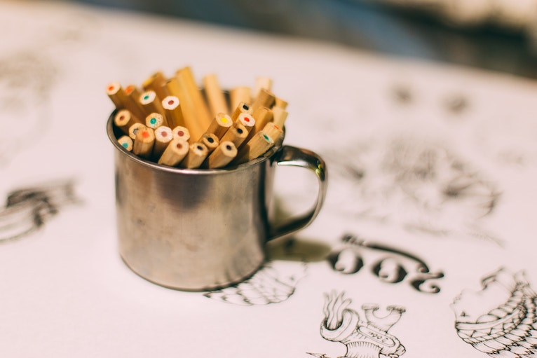 Tin cup filled with colored pencils