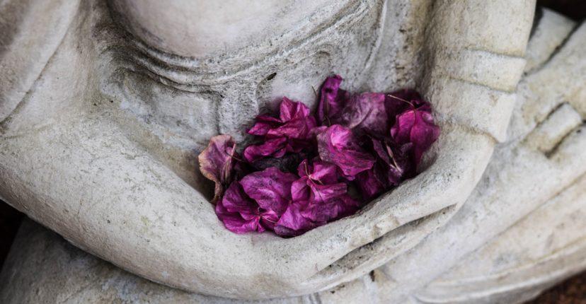 Buddha statue holding purple flowers