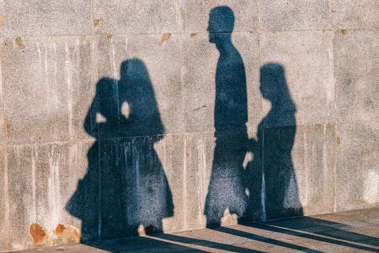 shadows of people on a concrete wall