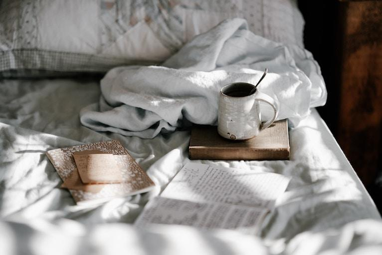 A rumpled bed with a cup of coffee and a book sitting on it.=