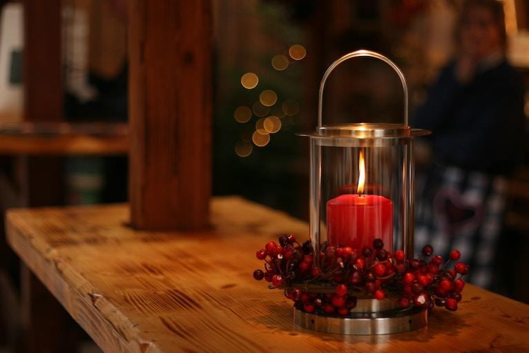 Candle surrounded by holly berries burning on a table