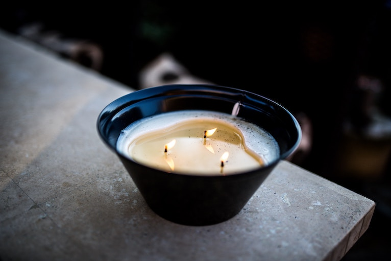 Rustic candle with three wicks burning in pottery bowl