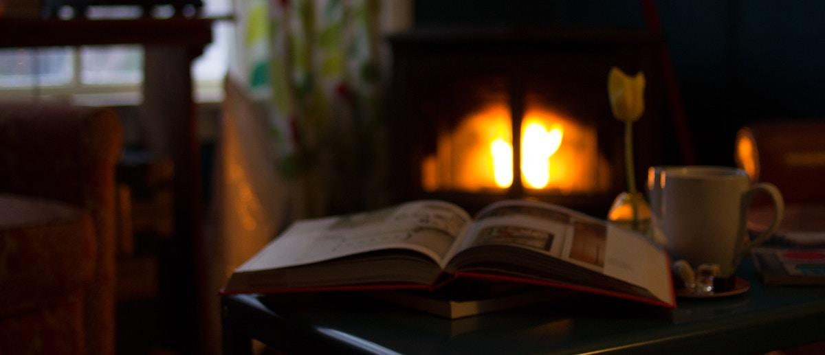winter cozy a book in front of a fireplace