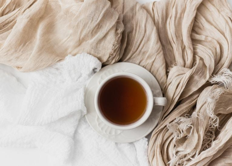 Cup of tea sitting on a bed, with a gauzy scarf