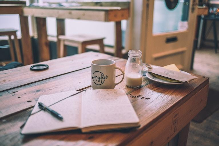 Coffee shop table with coffee and an open journal