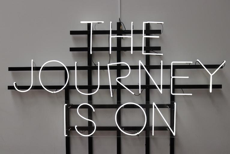 "Neon sign says ""The Journey is On"""