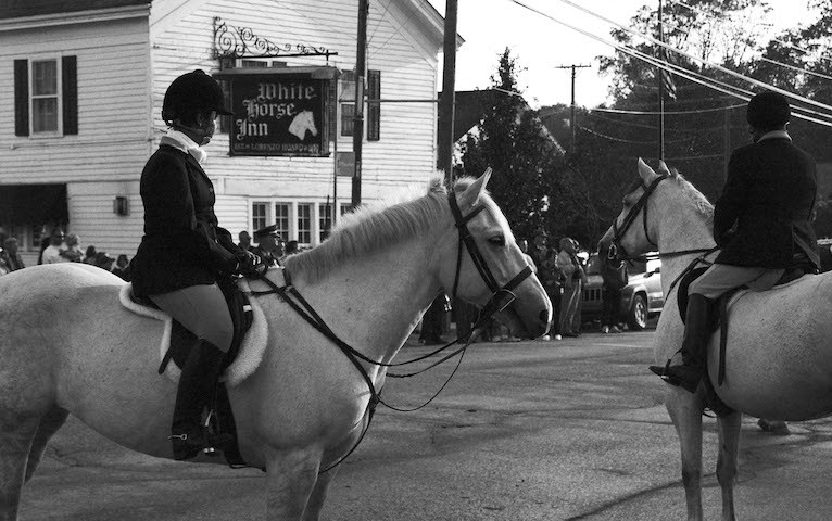 "women sit on horses outside ""The White Horse Inn"" during a hunt club event"